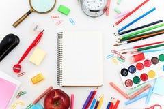 L'école a placé avec des carnets, des crayons, la brosse, des ciseaux et la pomme sur le fond blanc Photo libre de droits