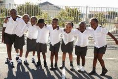 L'école primaire badine en Afrique posant dans le terrain de jeu d'école Photos libres de droits