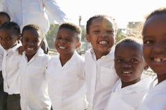 L'école primaire badine le sourire à l'appareil-photo dans le terrain de jeu Images stock