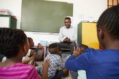 L'école primaire badine se reposer sur le plancher écoutant un professeur Photographie stock libre de droits