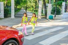 L'école primaire badine traverser la rue portant un gilet avec le sinus d'arrêt là-dessus photo stock