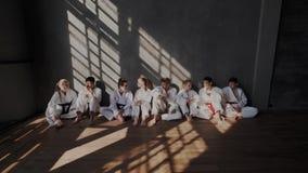 L'école traditionnelle de combat du Taekwondo Les enfants détendent et communiquent après un ensemble d'exercices pour combattre  banque de vidéos