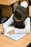 L'écolière écrit aux écriture-livres Photo stock