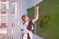 L'écolière écrit dans la craie sur un tableau noir images libres de droits