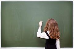 L'écolière écrit sur un tableau noir Photographie stock libre de droits