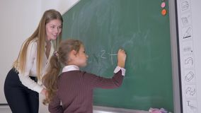 L'écolière avec le morceau de craie écrit un exemple sur le tableau noir avec l'aide d'un professeur féminin à la leçon de maths banque de vidéos