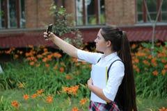 L'écolière de fille avec de longs cheveux dans l'uniforme scolaire fait le selfie photographie stock libre de droits