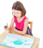 L'écolière de fille s'assied à une table image libre de droits