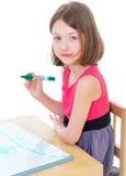 L'écolière de fille s'assied à une table photographie stock libre de droits