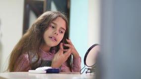 L'écolière de petite fille enduit la crème de visage L'adolescente de fille de soin de visage est enduite de la crème de visage à banque de vidéos