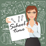 L'écolière de sourire se tenant devant un tableau noir et tenant une affiche avec l'école de ` d'expression chronomètrent le ` Photo stock