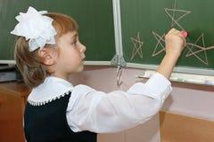 L'écolière dessine sur un panneau d'école Images libres de droits