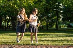 L'écolière deux de petite amie 7-8 années jouent avec des bulles de savon sur le pré en parc Image libre de droits