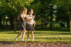 L'écolière deux de petite amie 7-8 années jouent avec des bulles de savon sur le pré en parc Images libres de droits
