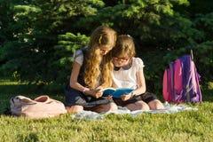 L'écolière deux de petite amie apprend se reposer sur un pré en parc Enfants avec des sacs à dos, livres, carnets Photographie stock