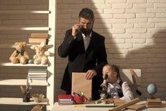 L'écolière et le papa avec les visages curieux tiennent le livre images stock