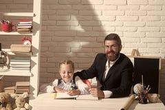 L'écolière et le papa avec les visages heureux se tenir écrivent dans le carnet photo libre de droits