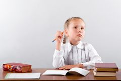 L'écolière pense au-dessus de la tâche difficile image stock