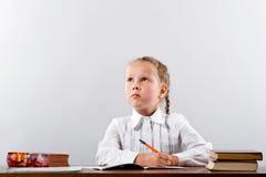 L'écolière pense au-dessus de la tâche difficile photos stock