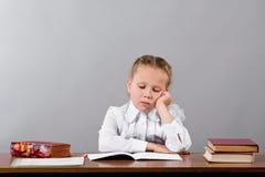 L'écolière pense au-dessus de la tâche difficile images libres de droits
