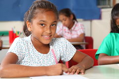 L'écolière primaire recherche du travail dans la salle de classe Image libre de droits