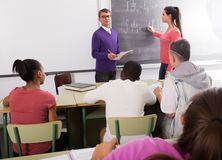 L'écolière résout la tâche près du tableau noir dans des mathématiques de salle de classe images libres de droits