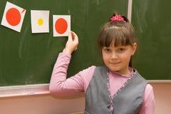 L'écolière restant à un tableau noir Photographie stock