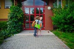 L'écolier avec le support d'écolière aux portes de l'école et au sujet de quelque chose murmurent Photo libre de droits