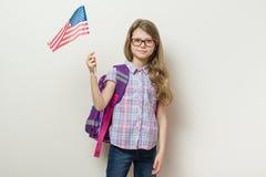 L'écolier avec un sac à dos tient le drapeau des Etats-Unis, mur lumineux de fond dans l'école Photographie stock libre de droits