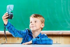 L'écolier font le selfie au tableau noir à l'école Image libre de droits