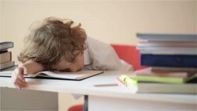 L'écolier font le travail Le garçon fait son travail à la maison l'élève a été ennuyé sur la leçon banque de vidéos