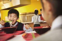 L'écolier mange des nouilles dans la cafétéria de l'école Image stock