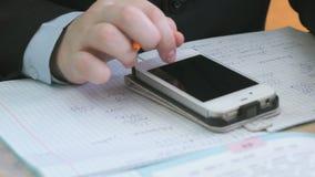 L'écolier regarde la formule utilisant le téléphone portable banque de vidéos