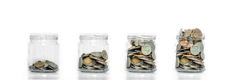 L'économie d'argent, le pot en verre arrangent avec des pièces de monnaie à l'intérieur de l'élevage, sur le fond blanc images stock