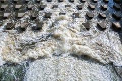 L'écoulement puissant de l'eau écumante se brise sur les pierre-brise-lames concrets près du barrage photos libres de droits