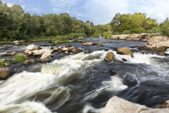 L'écoulement rapide de la rivière, des côtes rocheuses, de la rapide, de la végétation vert clair et d'un ciel bleu nuageux d'été Photo libre de droits