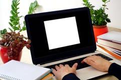 L'écran d'ordinateur portable avec une place blanche sur lui et la femme remet la dactylographie sur le clavier d'ordinateur port Photos stock