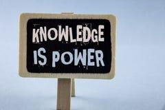 L'écriture conceptuelle de main montrant la connaissance est puissance L'étude de présentation de photo d'affaires te donnera l'a photos libres de droits