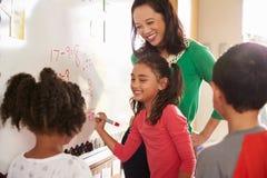 L'écriture d'élève sur le conseil aux maths d'école primaire classent photo stock