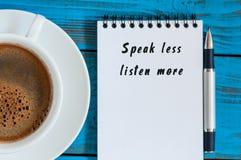 L'écriture d'homme d'affaires PARLENT ÉCOUTENT MOINS DAVANTAGE sur le bloc-notes près de la tasse de café de matin Avec l'espace  Images stock