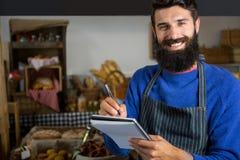 L'écriture de sourire de personnel masculin sur le bloc-notes au compteur dans la boulangerie font des emplettes Photos stock