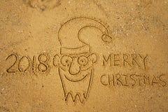 L'écriture exprime le JOYEUX NOËL 2018 sur le sable de la plage et le visage drôle du père noël Photographie stock