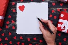 L'écriture femelle de main sur un livre blanc vide décoré de valen Images libres de droits