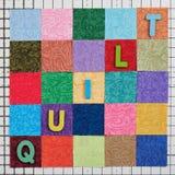 L'édredon de mot composé de lettres en bois colorées présentées sur les morceaux colorés de tissus disposés dans la forme de la p photo libre de droits