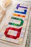L'édredon de mot cousu des morceaux colorés de place et de triangle de tissu photo libre de droits