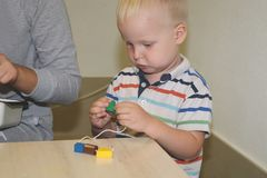 L'éducateur a affaire avec l'enfant dans le jardin d'enfants Créativité et développement de l'enfant images libres de droits