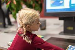 L'élève du cours préparatoire employant la technologie pour vérifier la bibliothèque réserve Photographie stock
