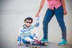 L'élève du cours préparatoire tombe plus de tout en faisant du roller avec la mère dans la PA Images stock