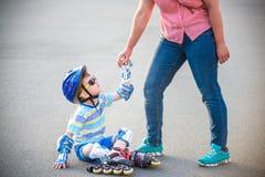 L'élève du cours préparatoire tombe plus de tout en faisant du roller avec la mère dans la PA Photographie stock