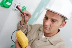 L'électricien assemble la prise murale bipolaire standard photo stock